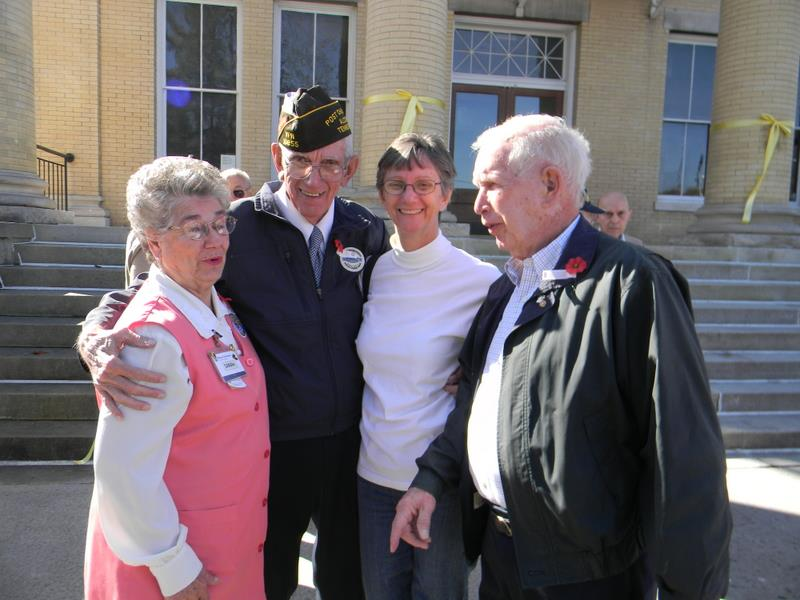 Two women and two men stand outside, together, smiling for camera